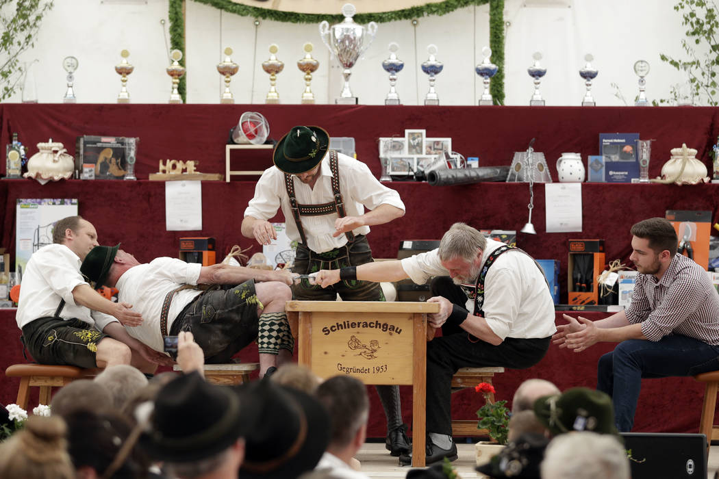A man dressed in traditional clothes tries to pull his opponent over the table at the 40th Alpine Country Championships in Fingerhakeln in Woernsmuehl, Germany, Thursday, May 25, 2017. Competitors ...