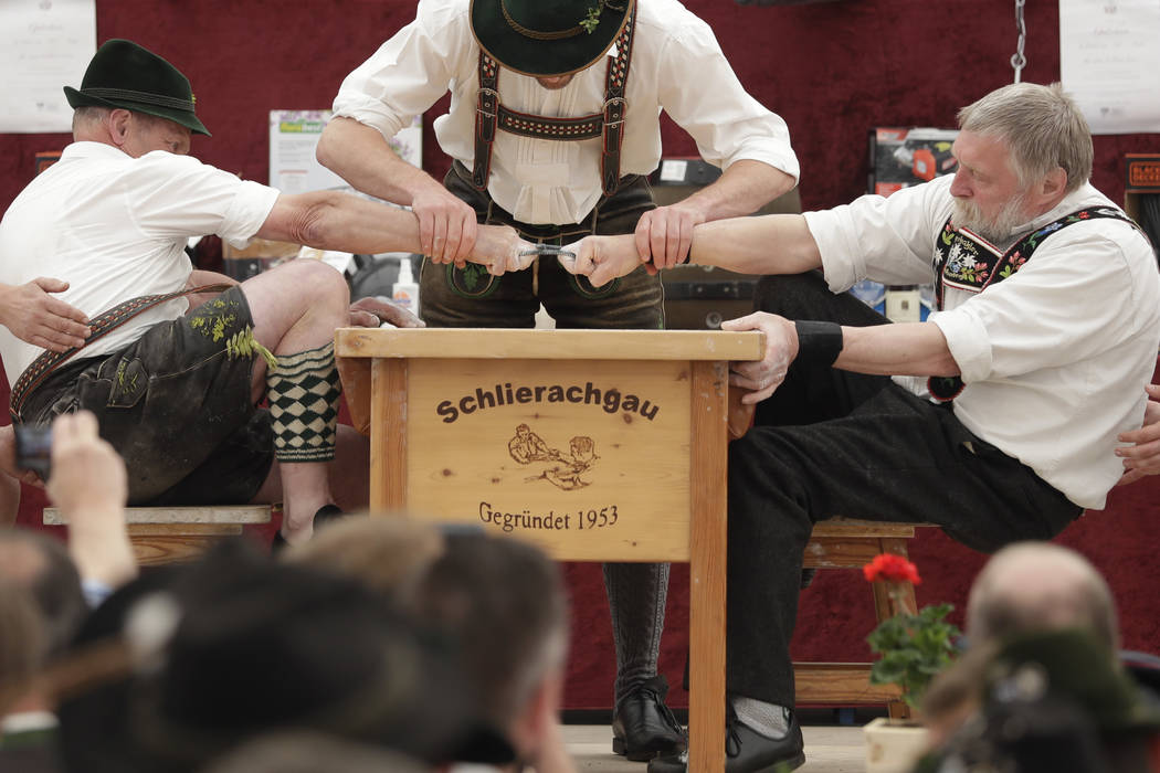 A man dressed in traditional clothes tries to pull his opponent over the table during the 40th Alpine Country Championships in Fingerhakeln_finger wrestling_ in Woernsmuehl, Germany, Thursday, May ...