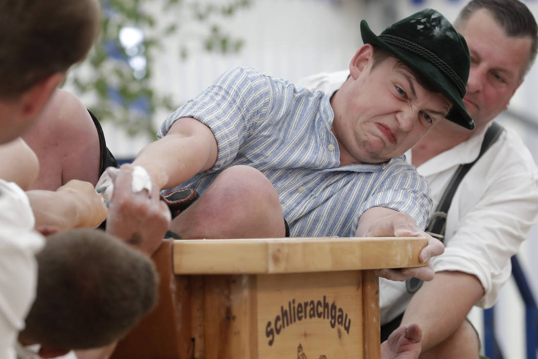 A man dressed in traditional clothes tries to pull his opponent over the table at the 40th Alpine Country Championships in Fingerhakeln_finger wrestling_ in Woernsmuehl, Germany, Thursday, May 25, ...