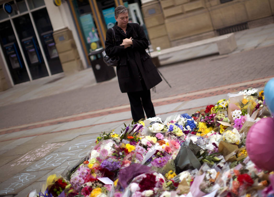 A woman stands by flowers offered for the victims of a suicide attack at a concert by Ariana Grande that killed more than 20 people Monday night in central Manchester, Britain, Wednesday, May 24,  ...