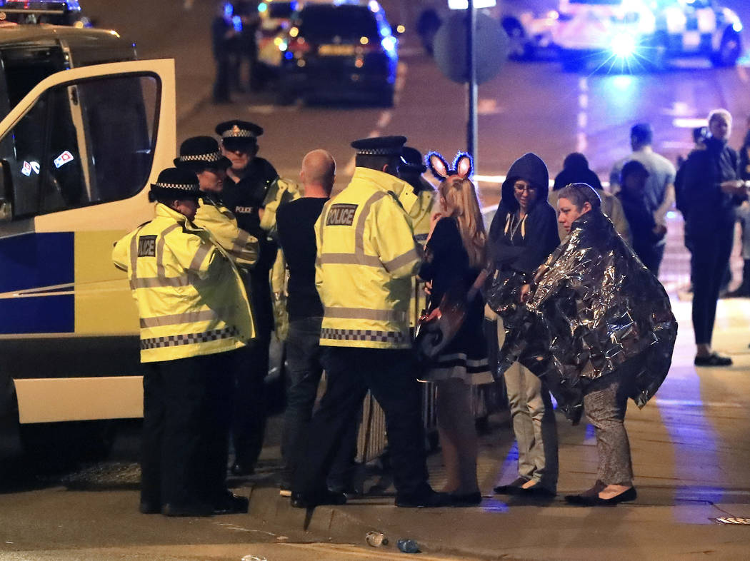 Emergency services personnel speak to people outside Manchester Arena after reports of an explosion at the venue during an Ariana Grande concert in Manchester, England, Monday, May 22, 2017. (Pete ...