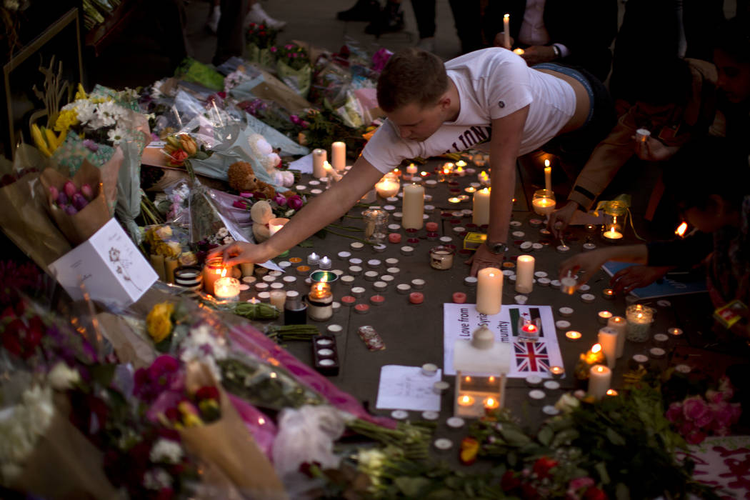 A man lights candles after a vigil in Albert Square, Manchester, England, Tuesday May 23, 2017, the day after the suicide attack at an Ariana Grande concert that left 22 people dead as it ended on ...