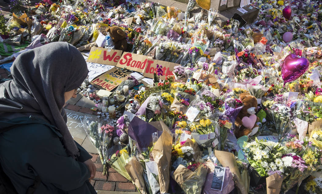 A woman looks at the floral tributes and messages left for the victims of the concert blast, during a vigil at St Ann's Square in central Manchester, England, Wednesday, May 24, 2017. &#xf ...