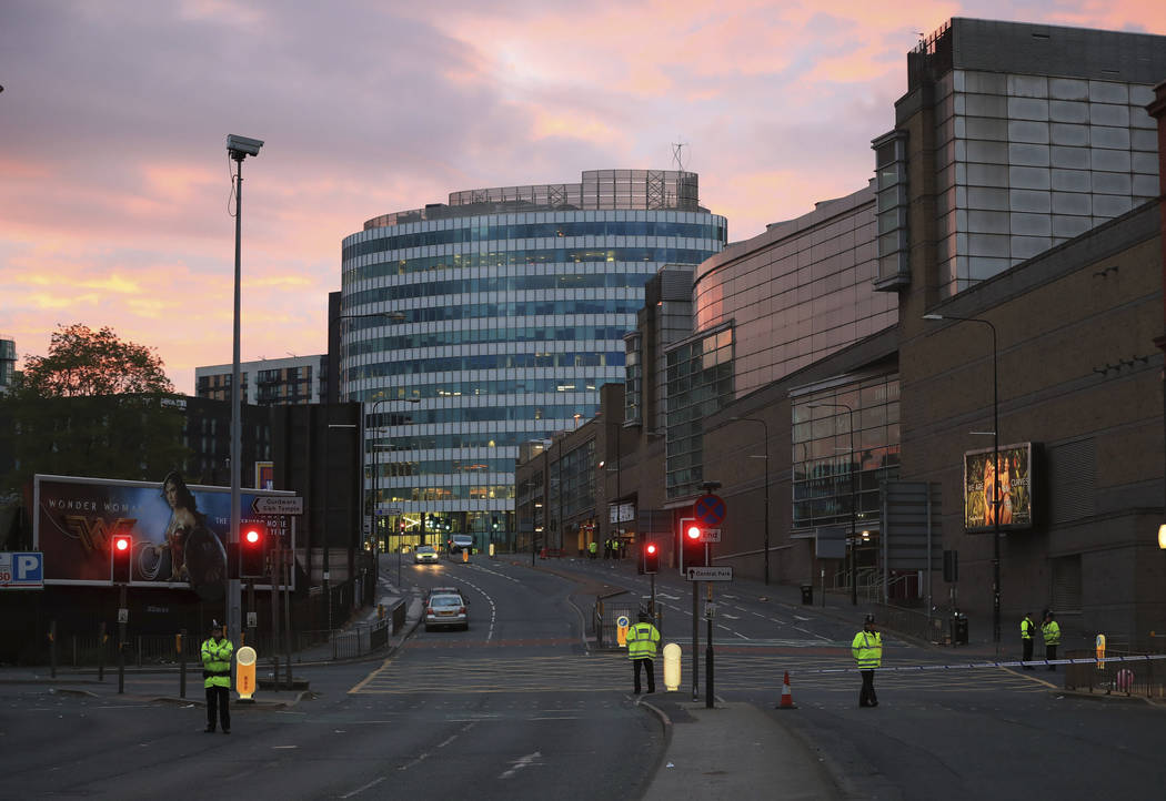 Police stand guard at dawn, after a blast at the Manchester Arena Tuesday, May 23, 2017. An explosion struck an Ariana Grande concert attended by thousands of young fans in northern England Monday ...