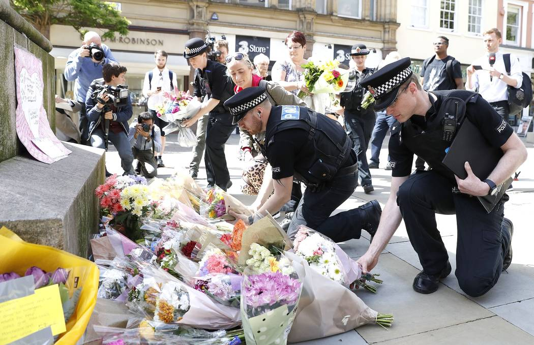 Police offices add to the flowers for the victims of Monday night pop concert explosion, in St Ann's Square, Manchester,  Tuesday May 23, 2017. A 23-year-old man was arrested in connection with Mo ...