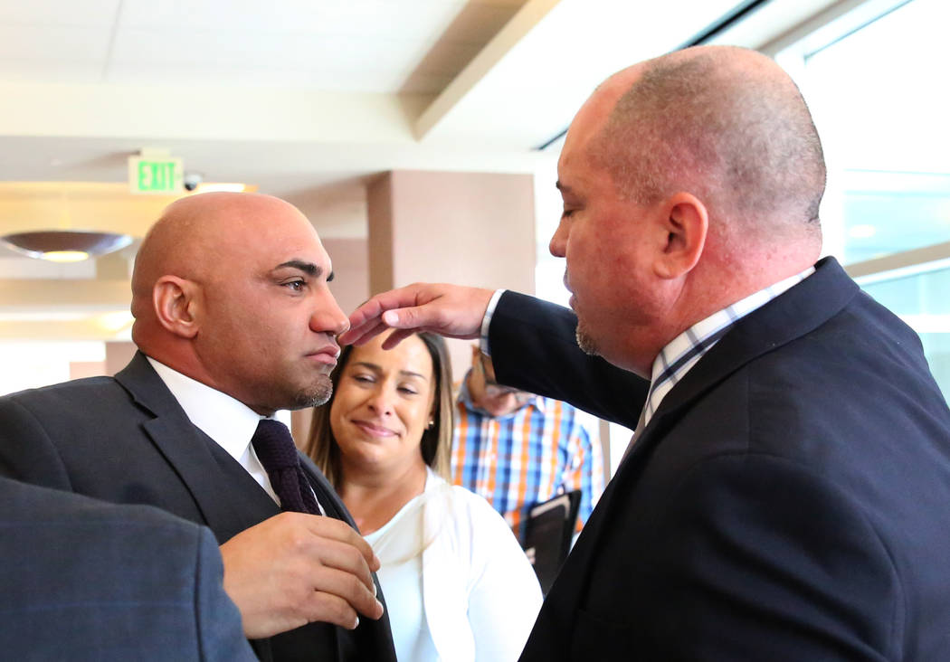Kenny Sanchez, Bishop Gorman's head football coach, left, prepares to hug his brother Tony Sanchez, UNLV head coach, after being found not guilty of domestic violence against his ex-girlfriend, at ...