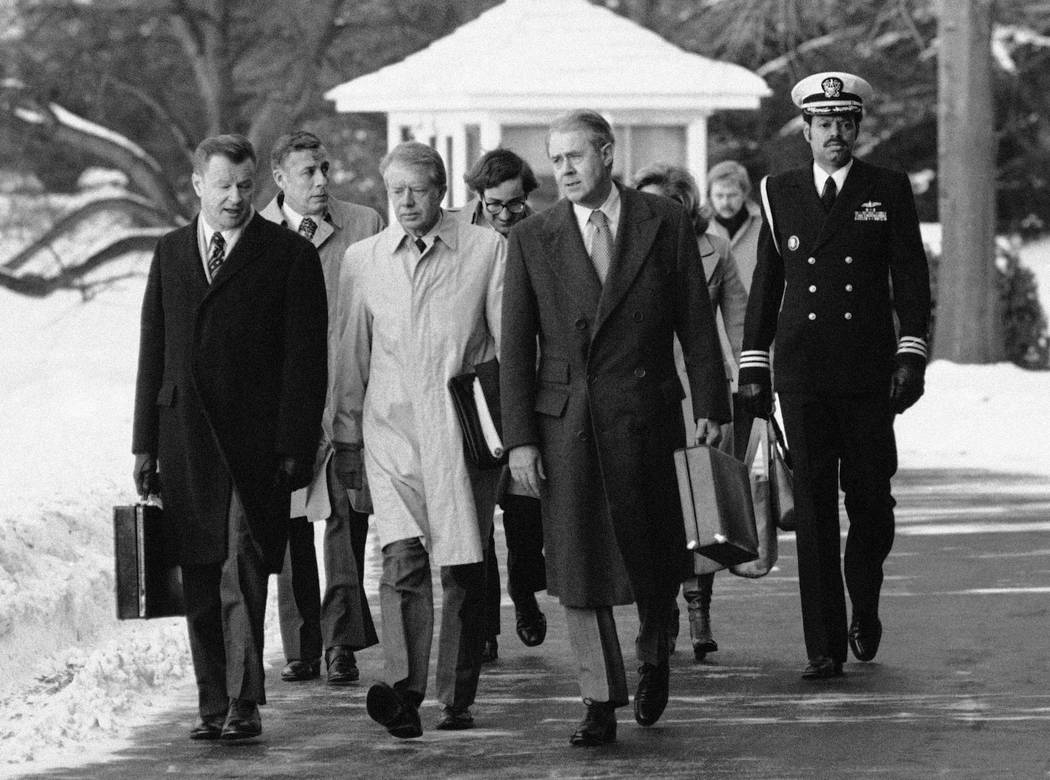 FILE - In this Feb. 14, 1979 file photo, President Jimmy Carter, flanked by Secretary of State Cyrus, right, and his advisor on foreign policy, Zbigniew Brzezinski, left, walk toward a waiting hel ...