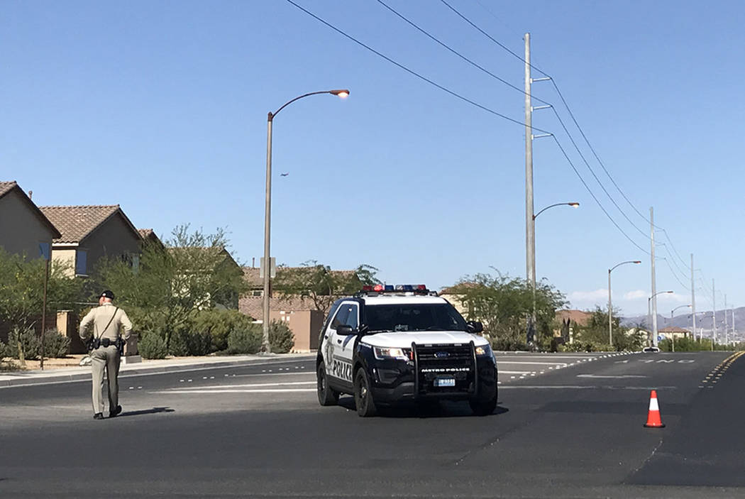 Police work the scene at Coldwater Creek Road and West Erie Avenue, near South Buffalo Drive, on Saturday after a juvenile riding a scooter was hit by a vehicle. (Rio Lacanlale/Las Vegas Review-Jo ...