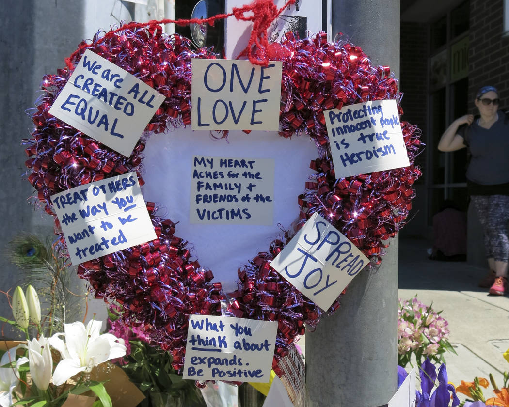 A heart-shaped wreath covered with positive messages hangs on a traffic light pole at a memorial for two bystanders who were stabbed to death Friday, while trying to stop a man who was yelling ant ...