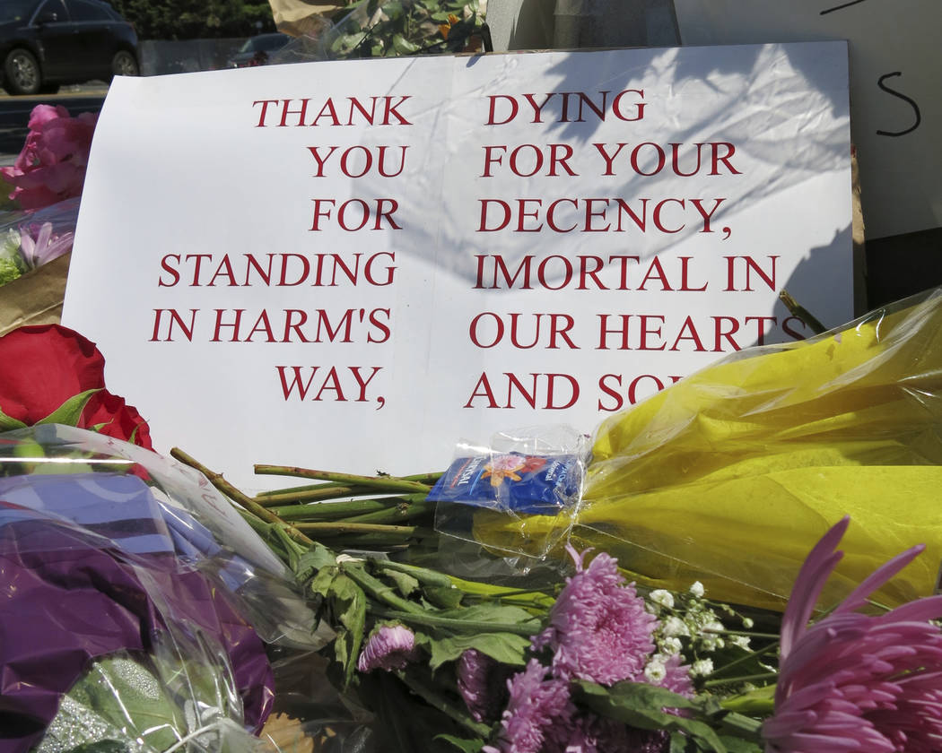 A sign of thanks rests against a traffic light pole at a memorial outside the transit center in Portland, Ore. on Saturday, May 27, 2017. People stopped with flowers, candles, signs and painted ro ...
