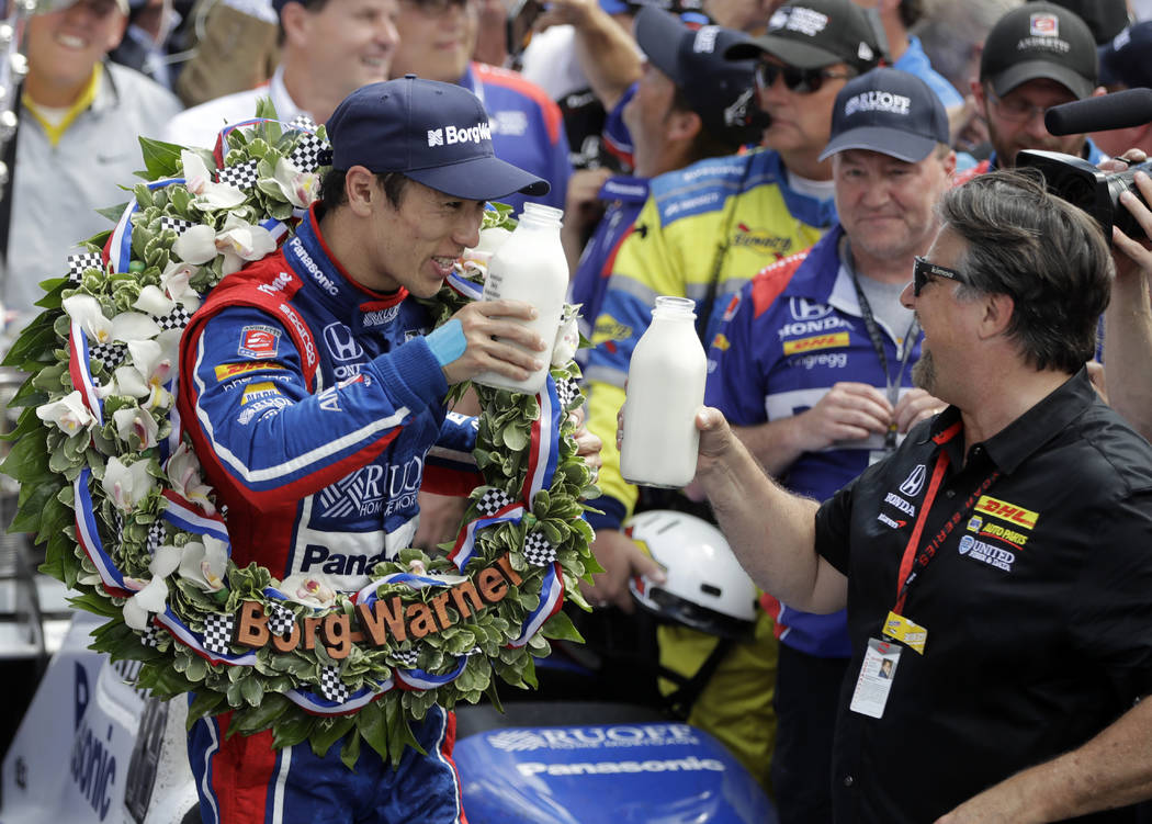 Takuma Sato, left, of Japan, toasts with car owner Michael Andretti as they celebrate after winning the Indianapolis 500 auto race at Indianapolis Motor Speedway, Sunday, May 28, 2017, in Indianap ...