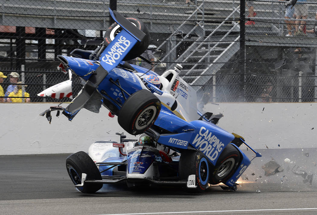 The car driven by Scott Dixon, of New Zealand, goes over the top of Jay Howard, of England, in the first turn during the running of the Indianapolis 500 auto race at Indianapolis Motor Speedway, S ...