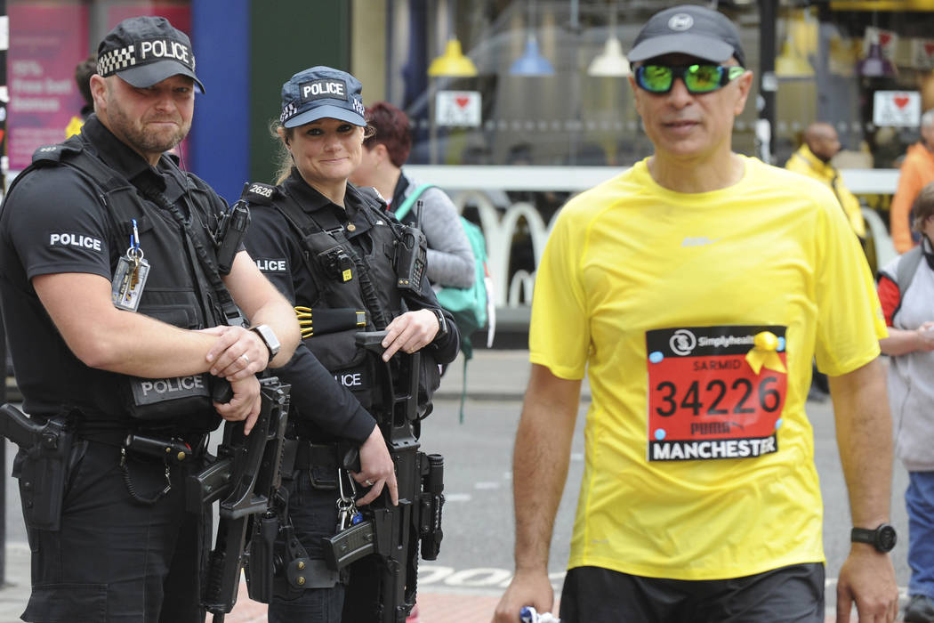 Armed response police guard the scene at the Great Manchester Run in central Manchester, England Sunday May 28 2017. More than 20 people were killed in an explosion following a Ariana Grande conce ...