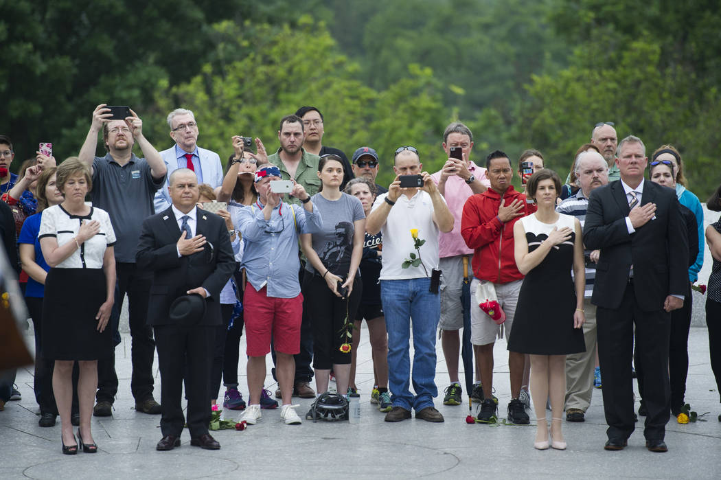 Visitors stand as Taps is played during a wreath laying ceremony at the grave of former President John F. Kennedy, to mark the 100th anniversary of his birth, at Arlington National Cemetery in Arl ...