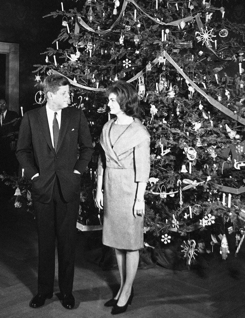 FILE - In this Dec. 13, 1961 file photo, President John F. Kennedy and his wife, Jacqueline, pose in front of the Christmas tree in the Blue Room of the White House in Washington. The occasion was ...