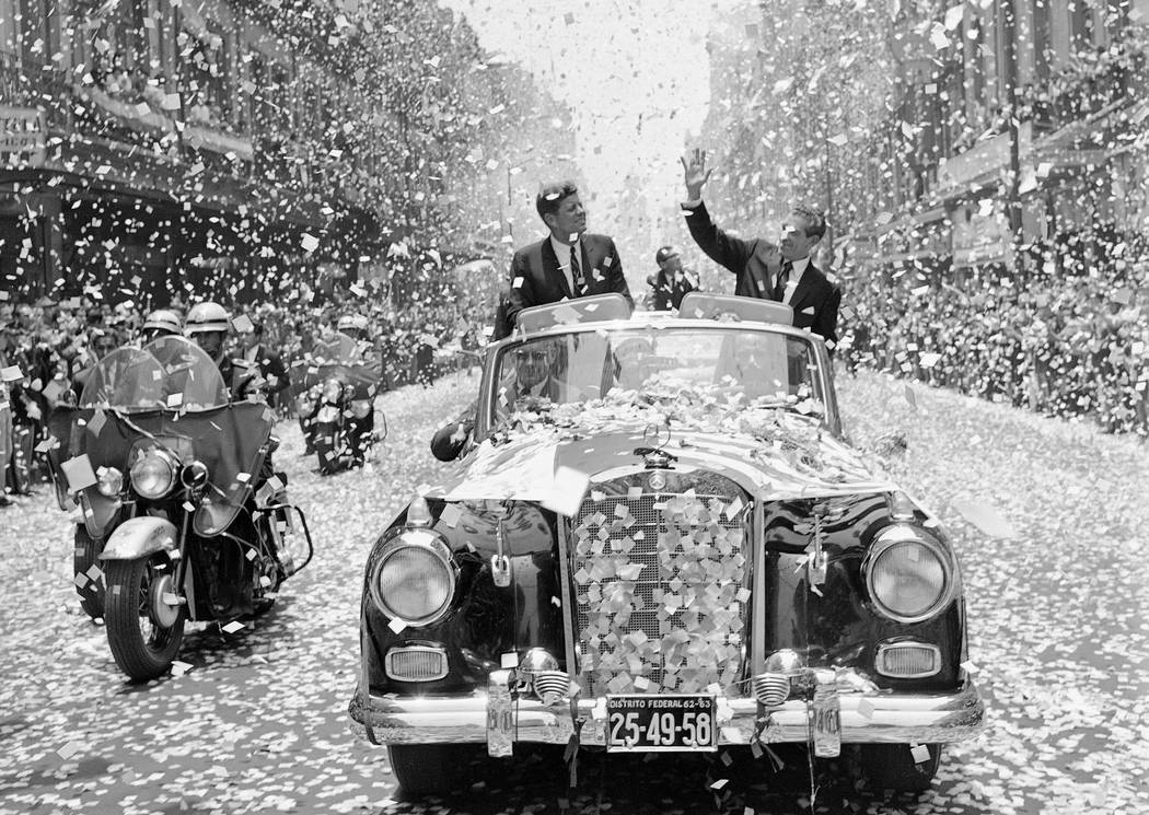In this June 29, 1962 file photo, U.S. President John F. Kennedy and Mexican President Adolfo Lopez Mateos are showered with confetti and paper as they travel down a boulevard in Mexico City, shor ...