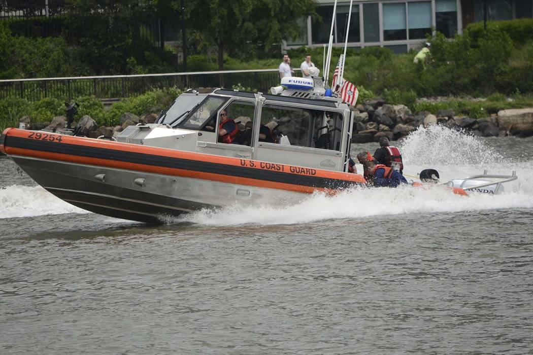 In this Sunday, May 28, 2017 photo, a Coast Guard crew tries to rescue a Navy Seal who fell into the Hudson River after his parachute failed to open during a Fleet Week demonstration over the rive ...
