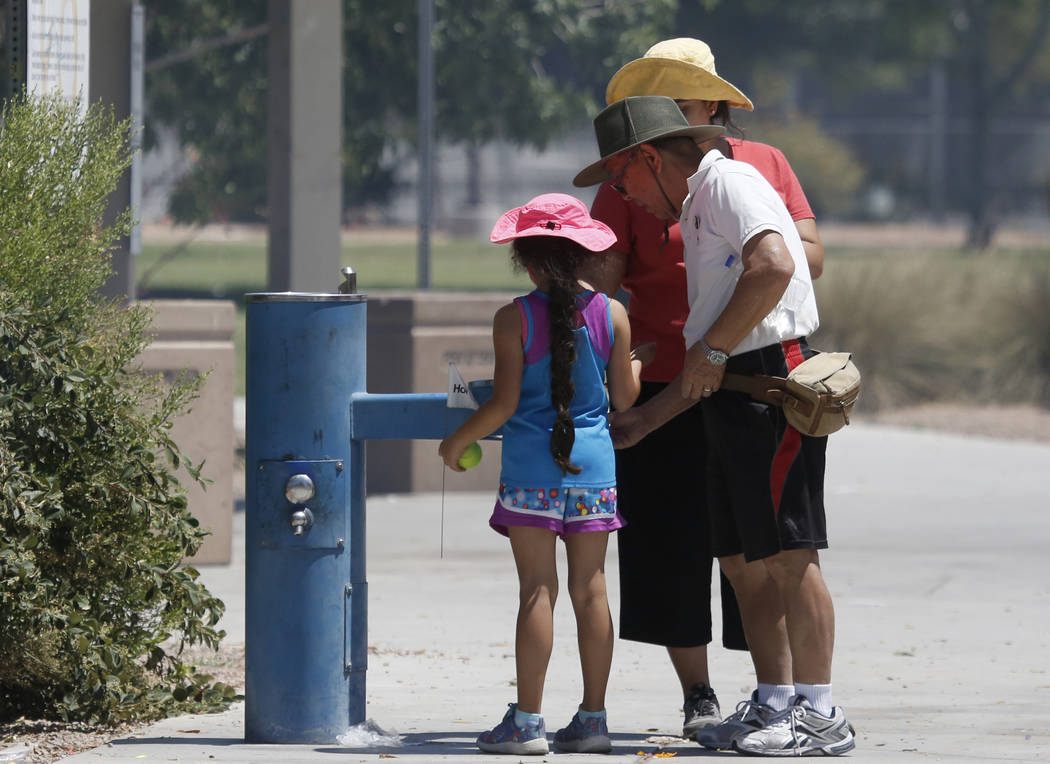 People, who declined to give their names, fill their water bottles from a water fountain at Lorenzi Park during a hot Memorial Day on Monday, May 29, 2017, in Las Vegas. (Bizuayehu Tesfaye/Las Veg ...