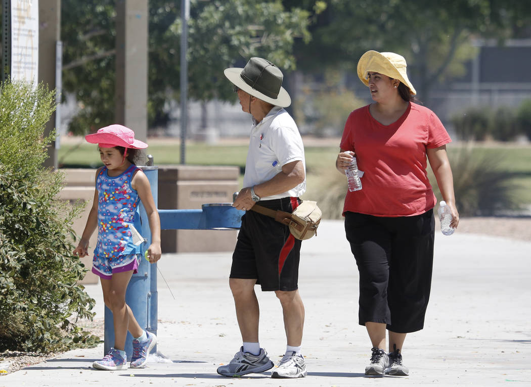 People, who declined to give their names, walk at Lorenzi Park during a hot Memorial Day on Monday, May 29, 2017, in Las Vegas. (Bizuayehu Tesfaye/Las Vegas Review-Journal) @bizutesfaye