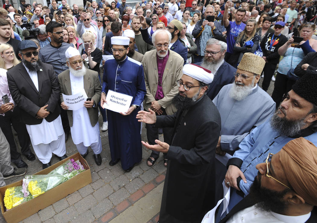 Members of the British Muslim Forum and religious leaders from Christian and Jewish faiths pay their respects at St Ann's square in Manchester, England Sunday May 28, 2017. The hunt is still on fo ...