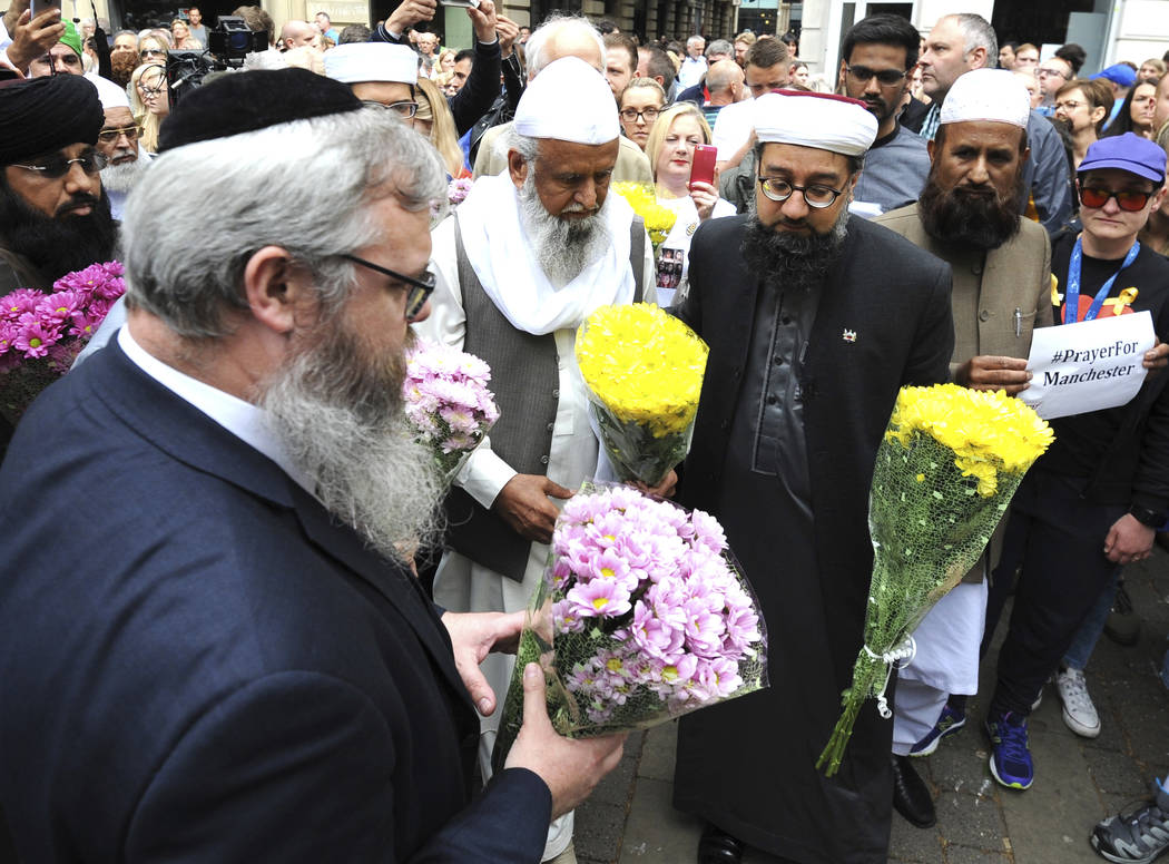 Members of the British Muslim Forum and religious leaders from Christian and Jewish faiths pay their respects at St Ann's square in Manchester, England Sunday May 28, 2017. (Rui Vieira/AP)