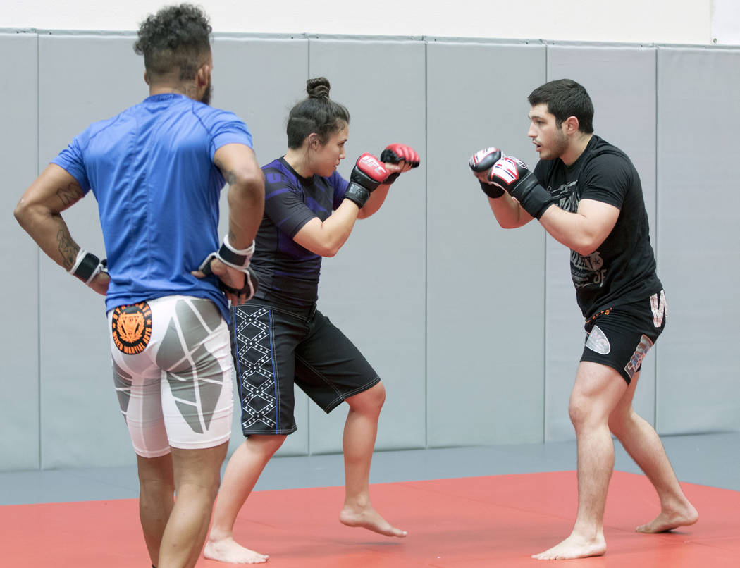 UFC strawweight Jamie Moyle, center, spars with Adam Acquaviva, right, as Donavon Frelow looks on at Syndicate MMA in Las Vegas on Wednesday, May 24, 2017. Heidi Fang/Las Vegas Review-Journal @Hei ...