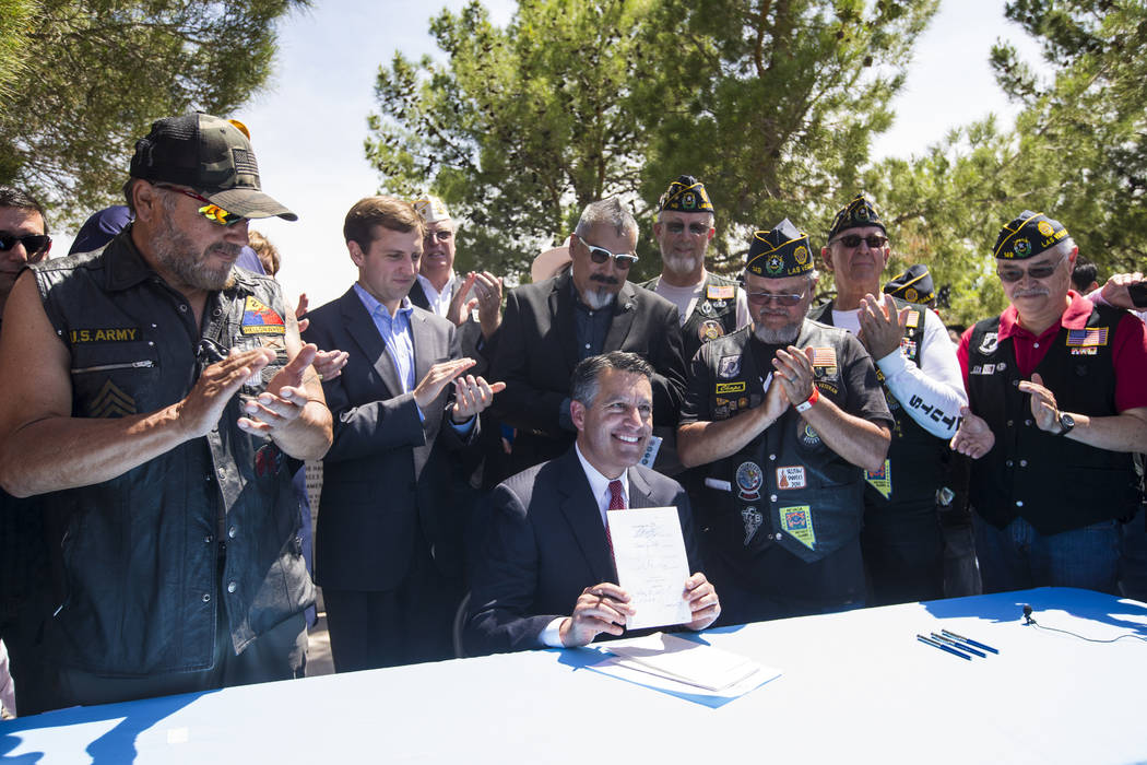 Gov. Brian Sandoval poses with a bill after signing it following a Memorial Day ceremony at the Southern Nevada Veterans Memorial Cemetery in Boulder City on Monday, May 29, 2017. Chase Stevens La ...