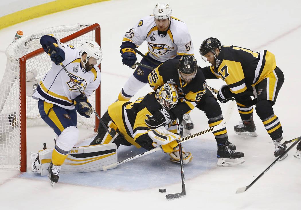 Pittsburgh Penguins' goalie Matt Murray, center, lunges toward the puck as Nashville Predators' Vernon Fiddler, left, and Cody McLeod contend during the first period in Game 1 of the NHL hockey St ...