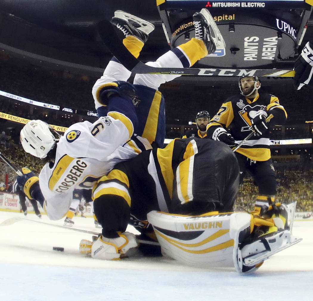 Nashville Predators' Filip Forsberg (9) lands on Pittsburgh Penguins' goalie Matt Murray (30) during the third period in Game 1 of the NHL hockey Stanley Cup Finals, Monday, May 29, 2017, in Pitts ...