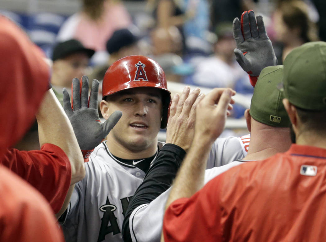Los Angeles Angels' Mike Trout is congratulated in the dugout after hitting a solo home run during the first inning of an interleague baseball game against the Miami Marlins, Saturday, May 27, 201 ...