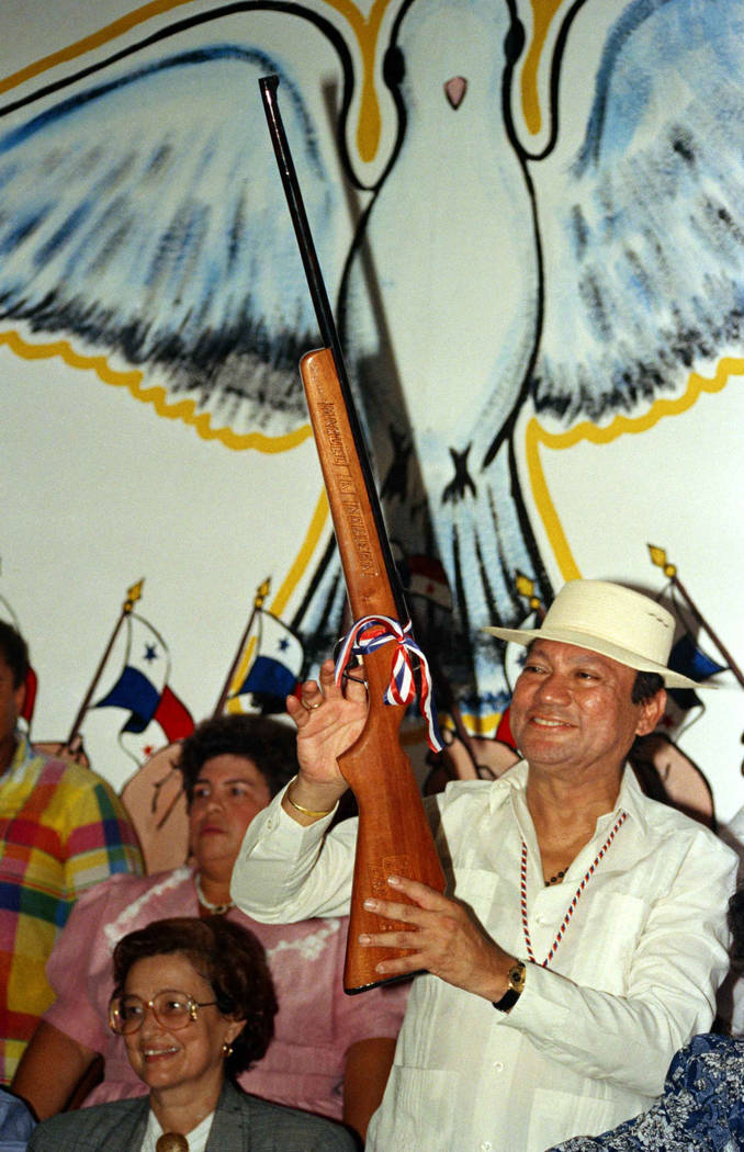 In this Oct. 5, 1989 file photo, Gen. Manuel Noriega holds a rifle bearing his name, given to him by a supporter during a pro-government rally, in Santiago, Panama. A source close to the family of ...