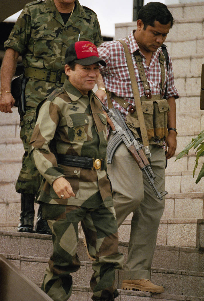 """In this Oct. 4, 1989 file photo, Gen. Manuel A. Noriega, center front, leaves defense forces headquarters in Panama City, accompanied by a member of an elite jungle fight army unit called """"Machos  ..."""