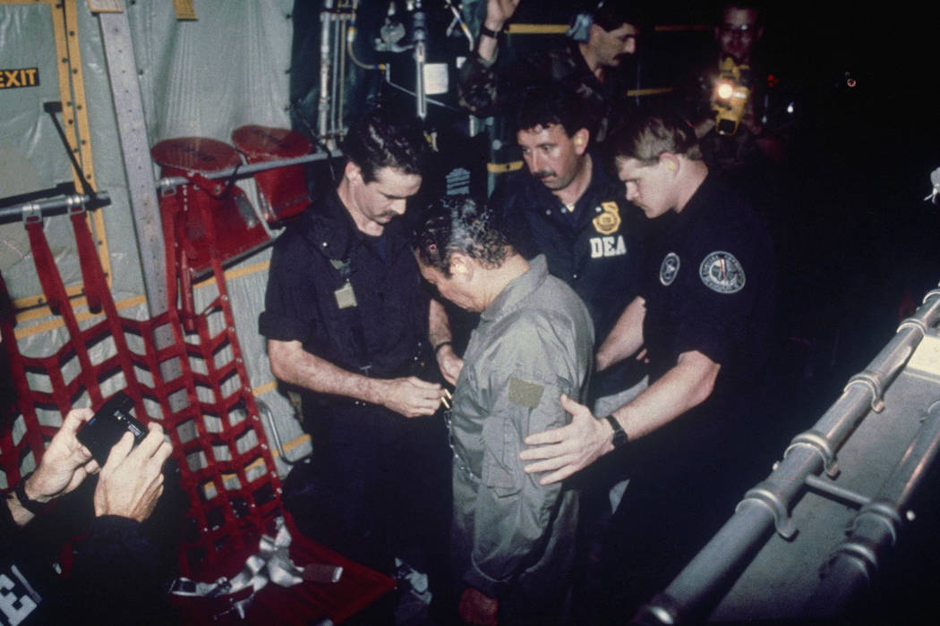 In this Jan. 4, 1990 file photo, Manuel Noriega watches as U.S. Drug Enforcement Agents place chains around his waist aboard a C-130 transport plane. A source close to the family of former Panaman ...