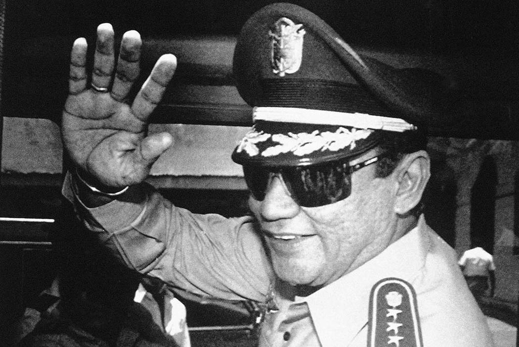 In this Aug. 31, 1989 file photo, Gen. Manuel Antonio Noriega waves to newsmen after a state council meeting, at the presidential palace in Panama City, where they announced the new president of t ...
