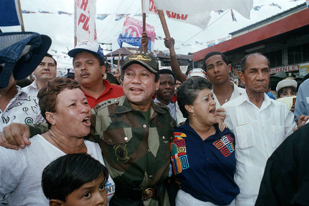 In this May 2, 1989 file photo, Gen. Manuel Antonio Noriega walks with supporters in the Chorrilo neighborhood, where he dedicated a new housing project, in Panama City. A source close to the fami ...