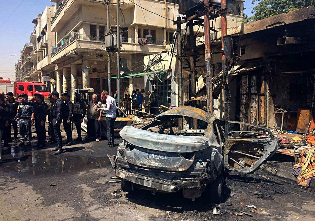 Iraqi security forces and civilians inspect the site of a deadly bomb attack, in Baghdad, Iraq, Monday, May 30, 2017. Another bomb exploded outside a popular ice cream shop in the Karrada neighbor ...