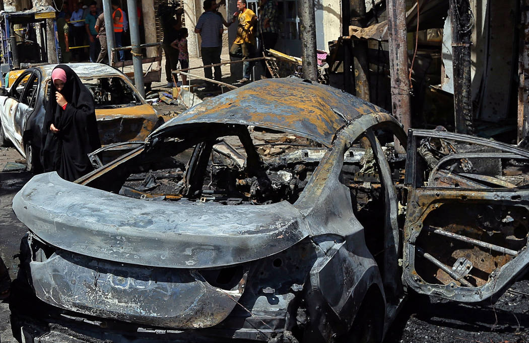 Civilians inspect the site of a deadly bomb attack, in Baghdad, Iraq, Monday, May 30, 2017. Another bomb exploded outside a popular ice cream shop in the Karrada neighborhood of Baghdad just after ...