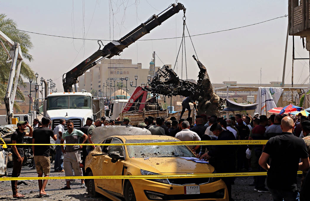 Iraqi security forces remove destroyed vehicles at the site of a deadly bomb attack, in Baghdad, Iraq, Monday, May 30, 2017. Another bomb exploded outside a popular ice cream shop in the Karrada n ...