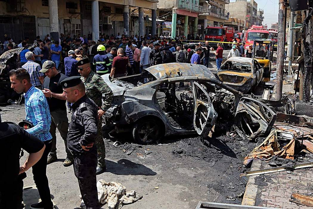 Iraqi security forces and civilians inspect the site of a deadly bomb attack, in Baghdad, Iraq, Monday, May 30, 2017. Another bomb exploded outside a popular ice cream shop just after midnight on  ...