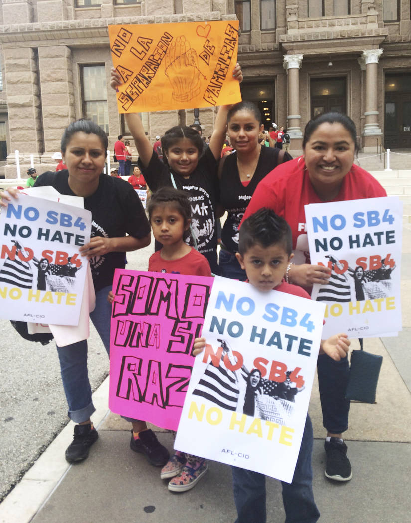 Rosario, right, and Marichuy, second from right in the back, demonstrate with family against a new Texas immigration law on Monday, May 29, 2017, in Austin, Texas. Opponents call Texas' anti-sanct ...
