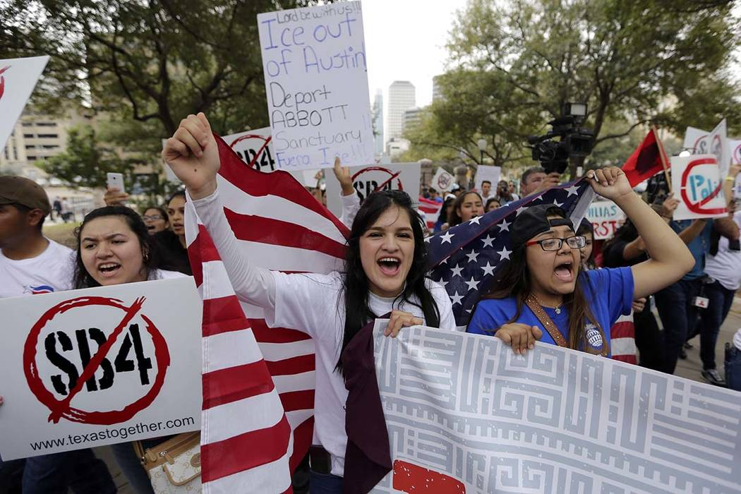 In this Feb. 28, 2017, file photo, Georgia Cordova of El Paso, Texas, center, joins other protesters as they take part in a No Ban, No Wall rally to support the rights of immigrants and oppose a b ...