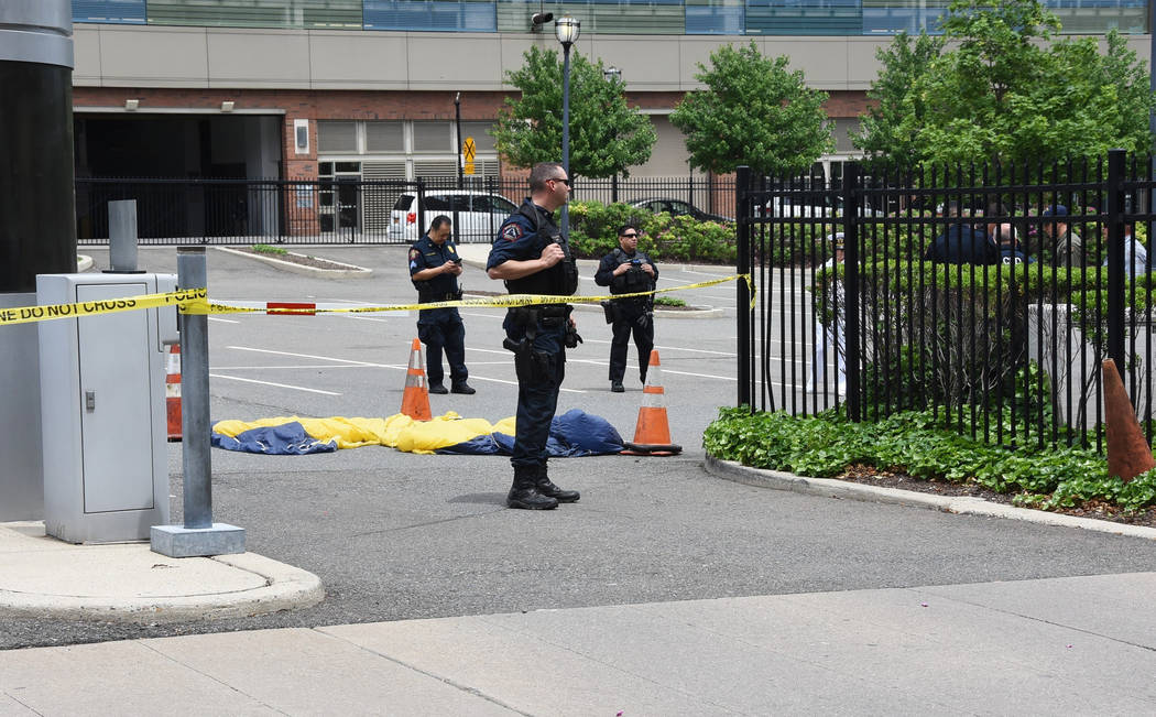Officials surround a U.S. Navy Seal's parachute that landed in a parking lot after the parachutist fell into the Hudson River when his parachute failed to open during a Fleet Week demonstration ov ...
