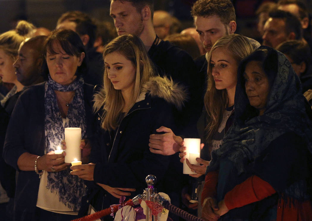 People light candles as they hold a minute's silence in St Ann's Square to mark the passing of exactly a week since the Manchester Arena concert blast, in Manchester, England, Monday May 29, 2017. ...