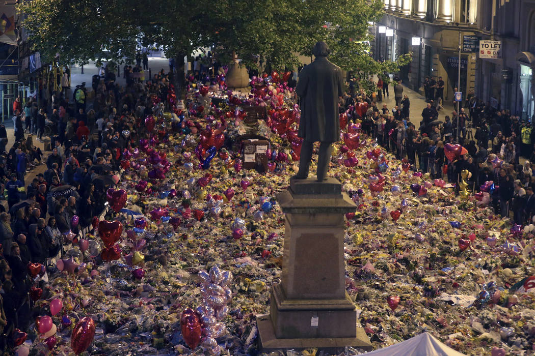 People view tributes to victims in St Ann's Square as they prepare to mark the passing of exactly a week since the Manchester Arena concert blast, in Manchester, England, Monday May 29, 2017. (Owe ...