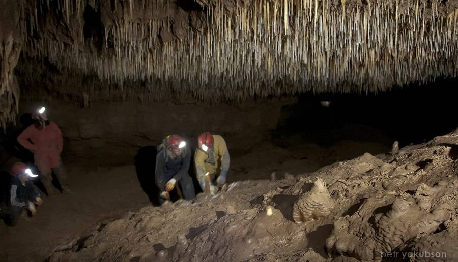 "Researchers examine a stalagmite for possible sampling inside Russia's Kinderlinskaya Cave in July 2012. ""We find a stalagmite we're willing to sacrifice, and we break it off,"" said UNLV doc ..."