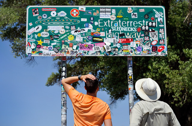Tourist Floris Otten, left, of The Netherlands, and Dean Baumgartner, of Adventure Photo Tours look over all the stickers covering the Extraterrestrial Highway sign on Tuesday, Aug. 5, 2014. (Davi ...