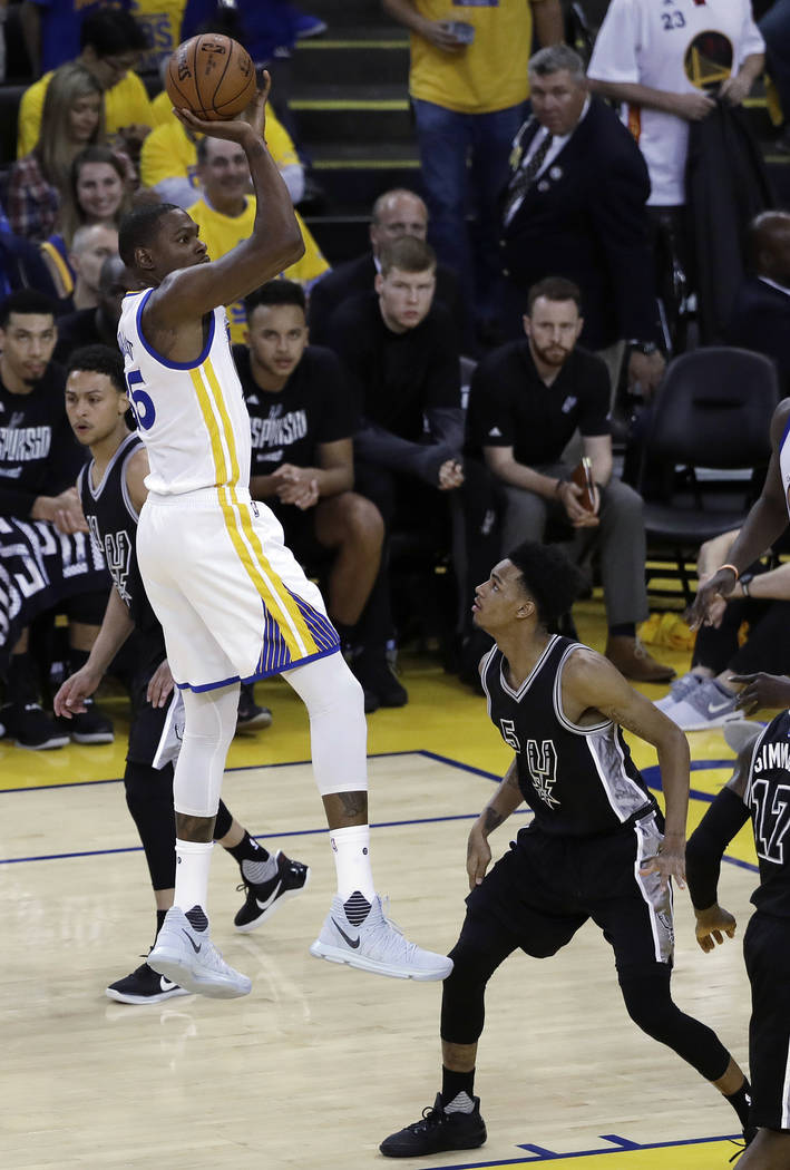 Golden State Warriors' Kevin Durant shoots over San Antonio Spurs' Dejounte Murray, right, during the first half of Game 2 of the NBA basketball Western Conference finals, Tuesday, May 16, 2017, i ...