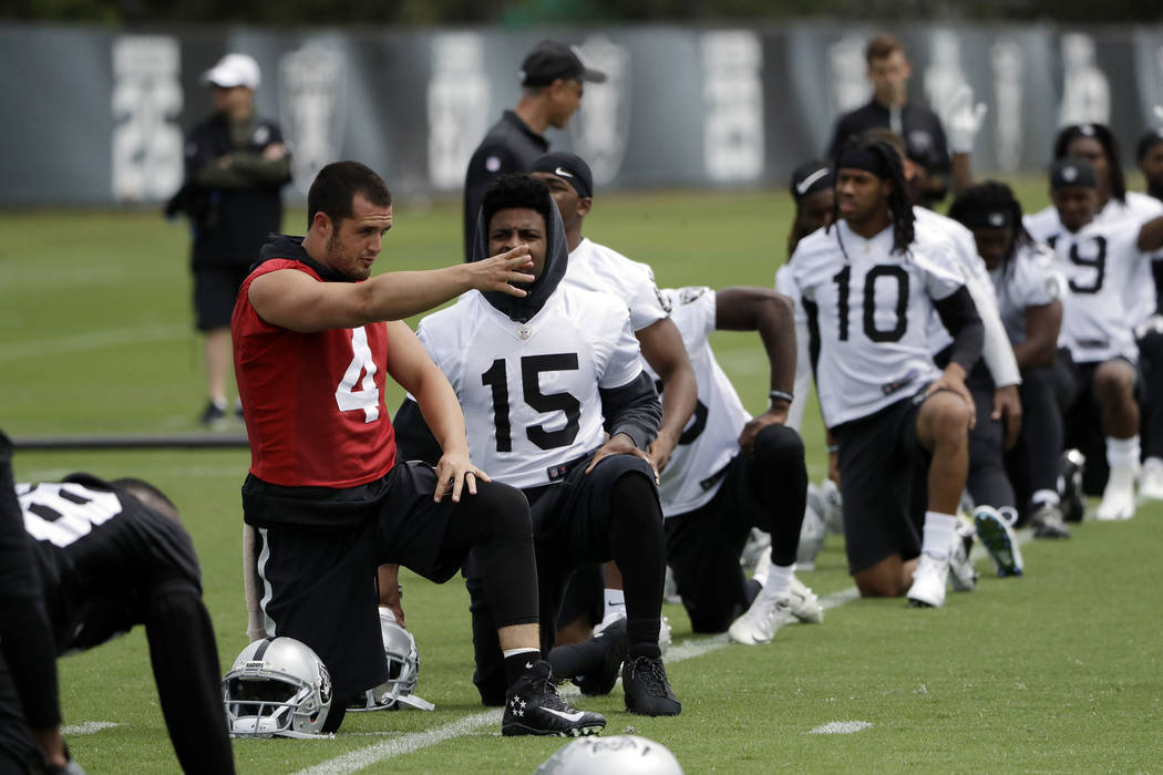 Oakland Raiders quarterback Derek Carr (4) talks to wide receiver Michael Crabtree (15) during the team's organized team activity at its NFL football training facility Tuesday, May 30, 2017, in Al ...