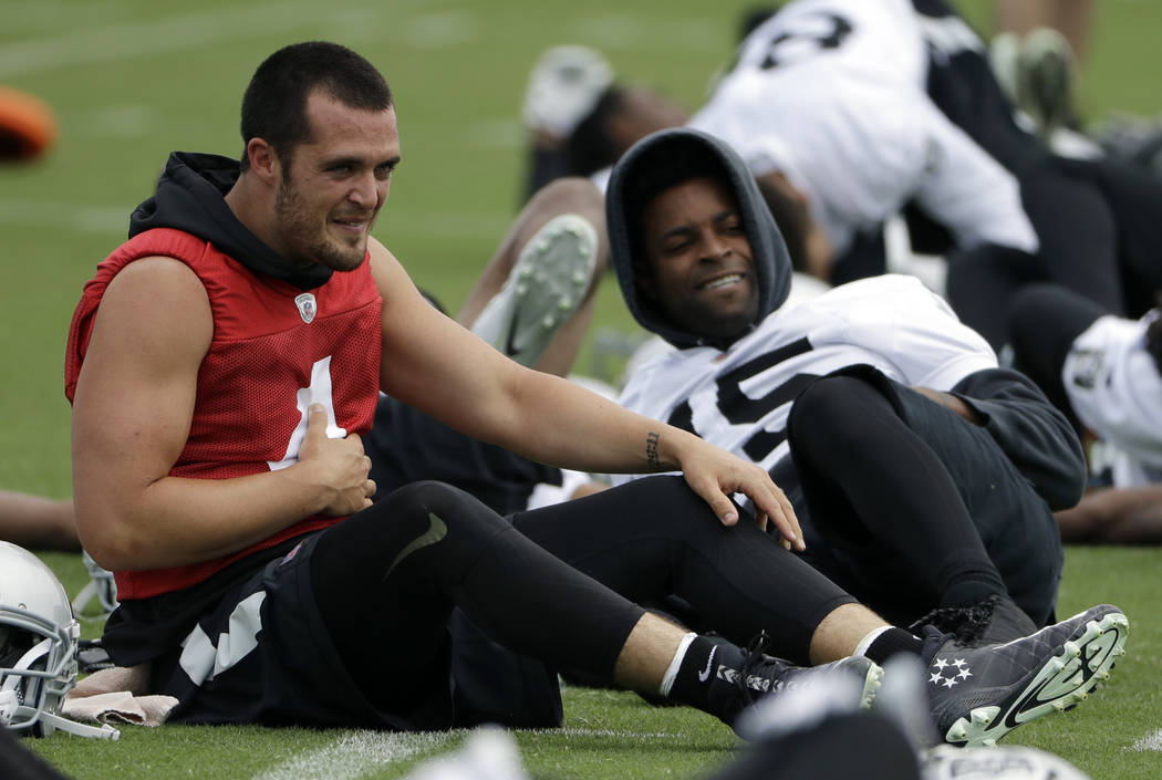 Oakland Raiders quarterback Derek Carr (4) stretches with teammate Michael Crabtree during the team's organized team activity at its NFL football training facility Tuesday, May 30, 2017, in Alamed ...