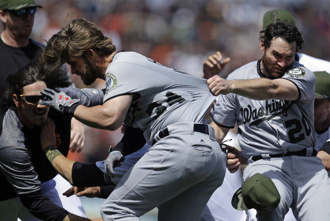 Washington Nationals' Daniel Murphy (20) tries to restrain teammate Bryce Harper (34) after Harper charged San Francisco Giants' Hunter Strickland after being hit with a pitch in the eighth inning ...